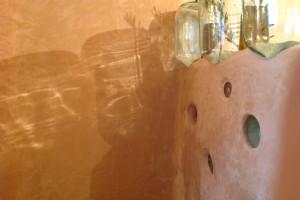 dettaglio tadelakt e bottiglioni recuperati nella zona doccia